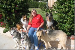 Photo of Patty Thurner sitting with five dogs